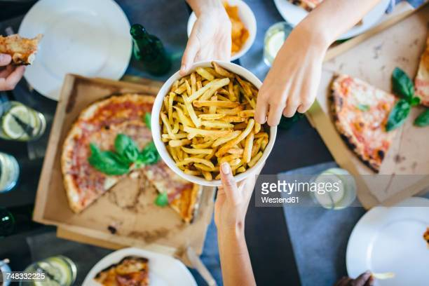 hand taking french fries from bowl - take away food stock pictures, royalty-free photos & images