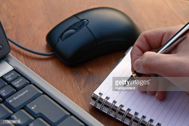 A hand taking notes beside a mouse and a laptop computer
