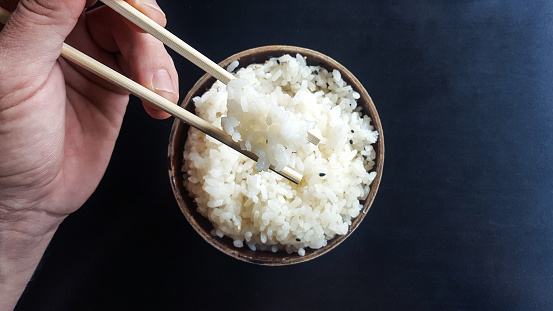 Hand taking some white rice with chopsticks - gettyimageskorea