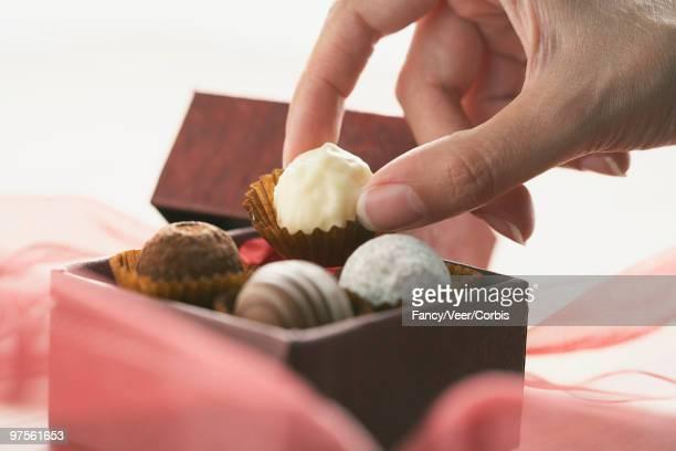 Hand taking white chocolate truffle