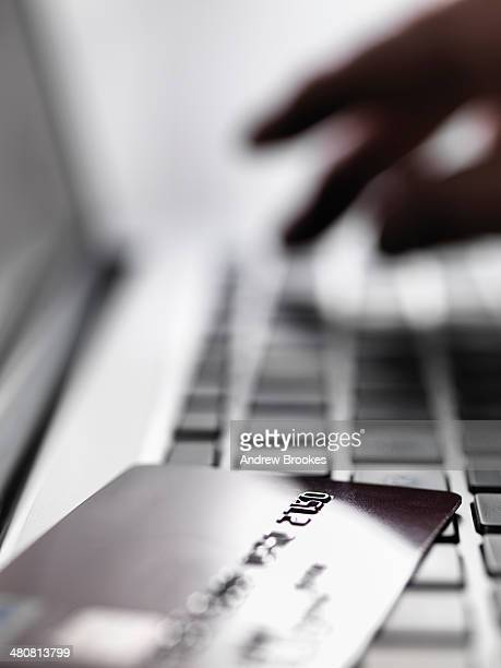 Hand tapping account details on laptop to illustrate internet shopping and internet fraud