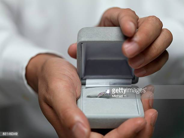 hand that presents ring - engagement ring box stock photos and pictures