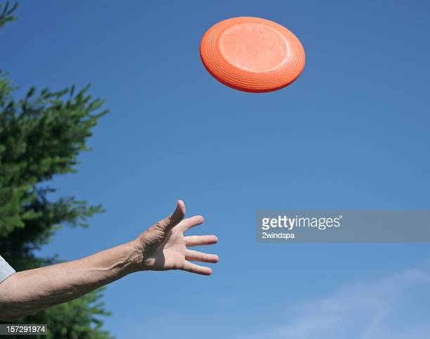 A hand throwing a Frisbee in the air