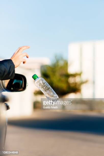 Hand throwing bottle out of car window.