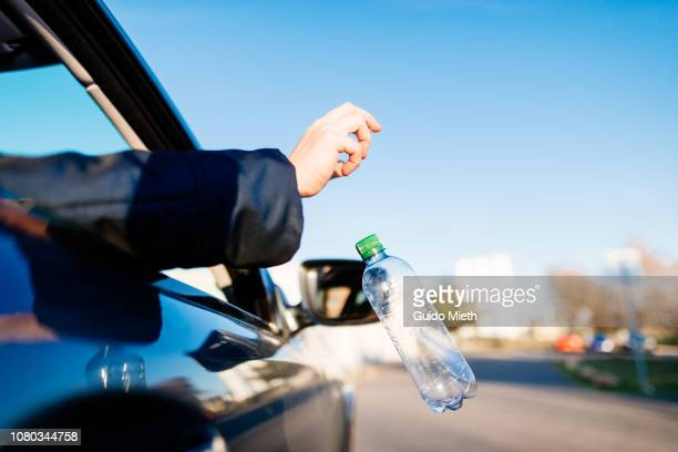 hand throwing garbage out of car window. - alleen één mid volwassen vrouw stockfoto's en -beelden