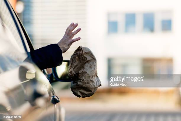 Hand throwing garbage out of car window.