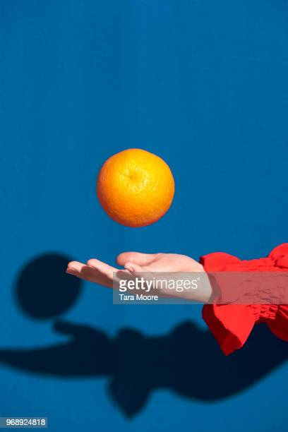 hand throwing orange in air - single object stock pictures, royalty-free photos & images