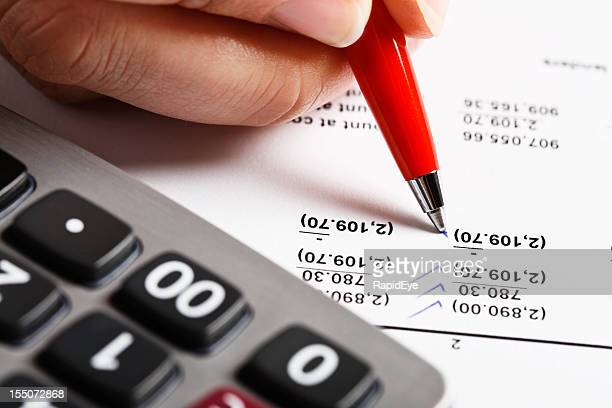Hand ticks off figures on spreadsheet, calculator standing by