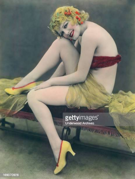 A hand tinted photograph of a scantily clad smiling woman sitting on a bench 1930