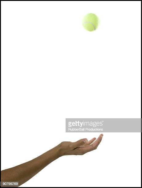 hand tossing a tennis ball