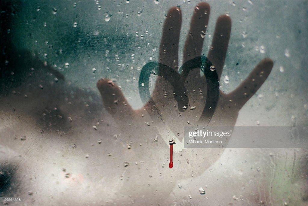 Hand touching a broken heart on a rainy window : Stock Photo