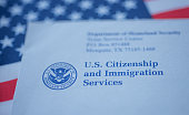 Hand touching Letter (Envelope) from USCIS on  flag of USA background.
