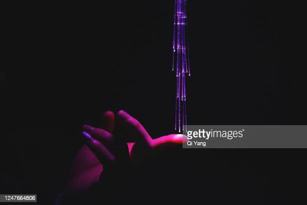 hand touching red fiber optics - sensor stock pictures, royalty-free photos & images