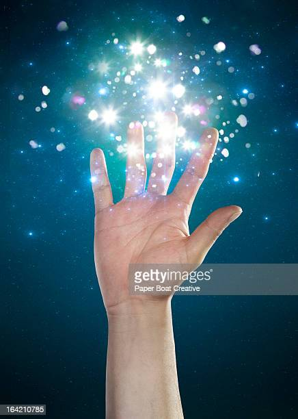 hand touching sparkles and abstract glow