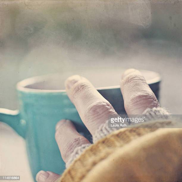 Hand touching  warm steaming cup of coffee