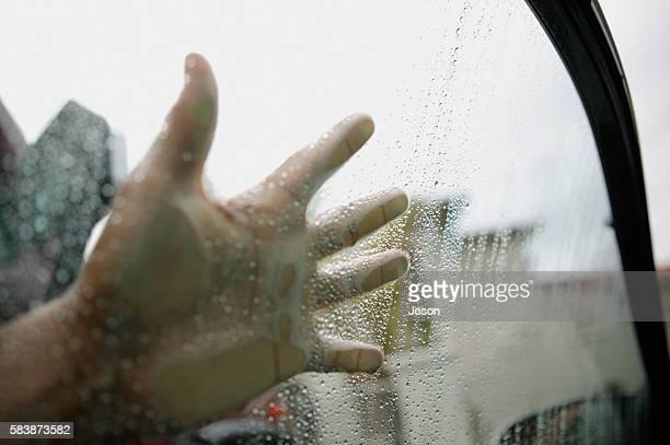 Hand touching wet car window glass