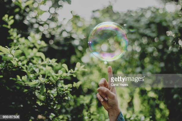 Hand trying to catch  soap bubbles