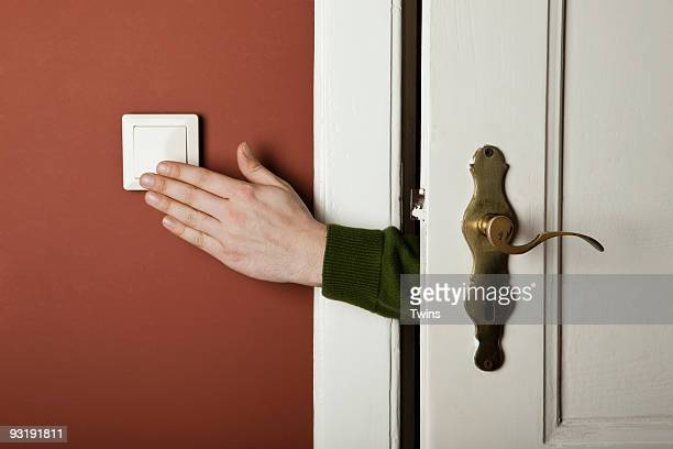 A hand turning off a light switch