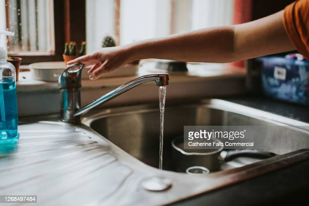 hand turning off a running chrome tap in a kitchen - flowing water stock pictures, royalty-free photos & images