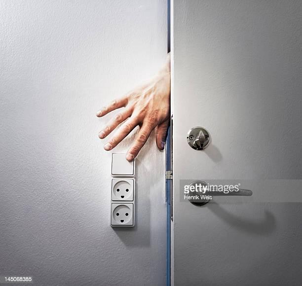 Hand turning off light from behind door