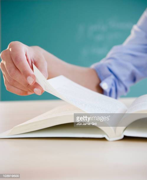Hand turning page in book