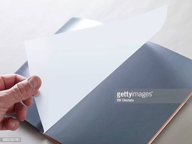hand turning page on blank book.