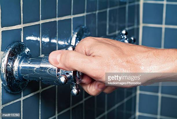 Hand turning water faucet in shower, close-up