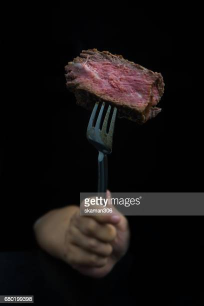 hand use Fork  cut tenderloin beef steak