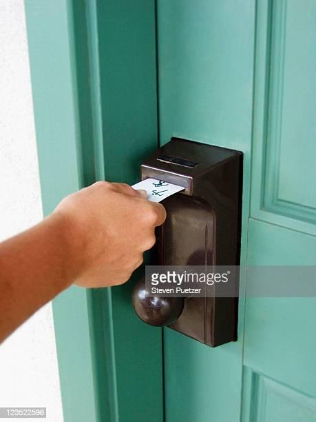 Hand using card key to open door