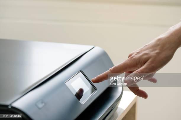 hand using computer printer - cris cantón photography fotografías e imágenes de stock