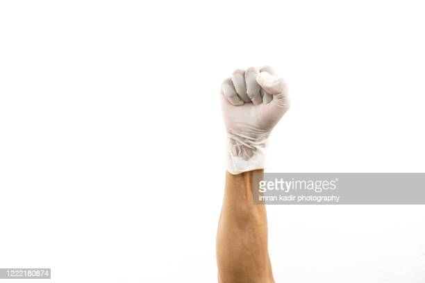hand using latex glove showing fist or supporter and success sign. - human arm fotografías e imágenes de stock