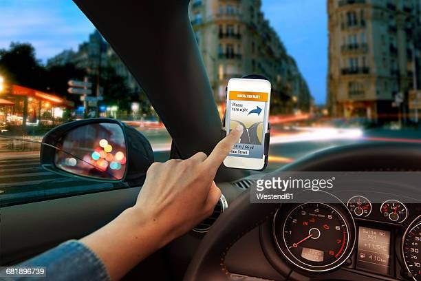 Hand using mobile phone navigation app in car