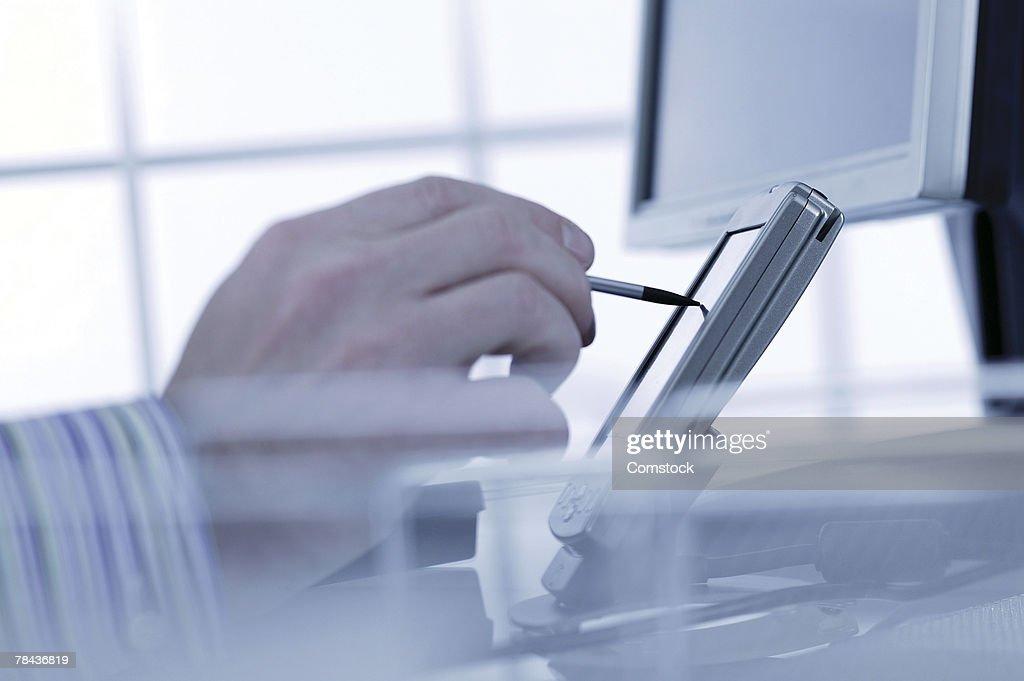 Hand using PDA on desk : Stockfoto