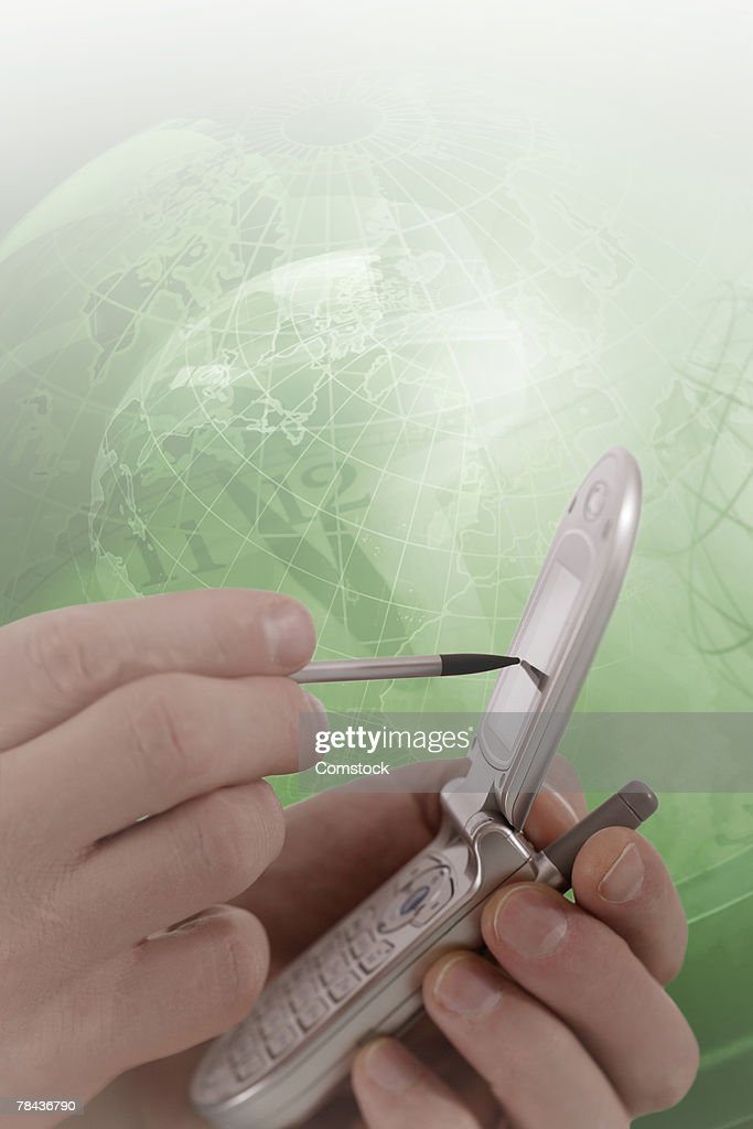 Hand using PDA with world map behind it : Stockfoto