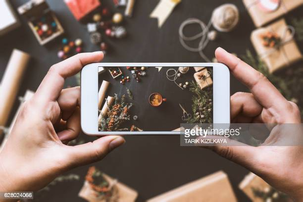 Hand using smartphone, sharing Christmas preparation on social media