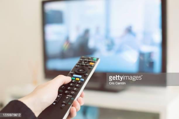 hand using tv remote control - cris cantón photography fotografías e imágenes de stock