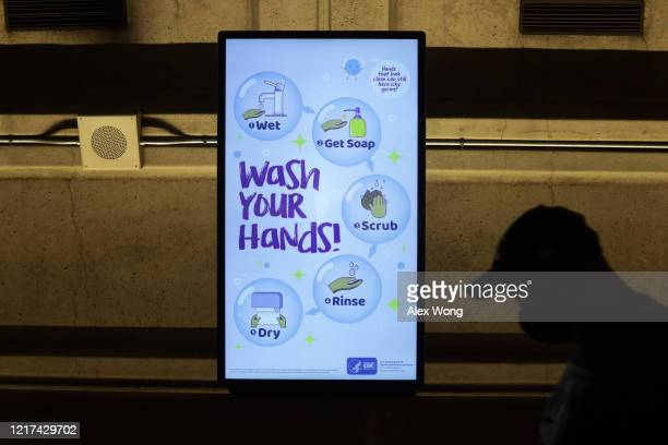 CDC hand washing guideline is seen on a screen as a passenger passes by at Metro Center Station April 7 2020 in Washington DC Washington Metropolitan...