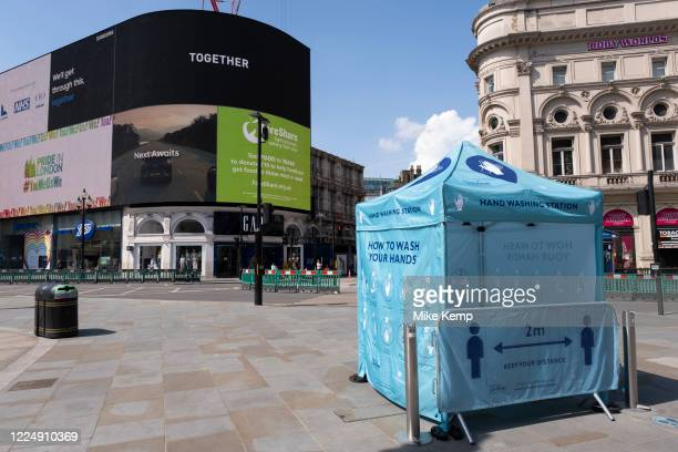 Hand washing station at Piccadilly Circus which remains very quiet under coronavirus lockdown, with the famous advertising screens half filled with...