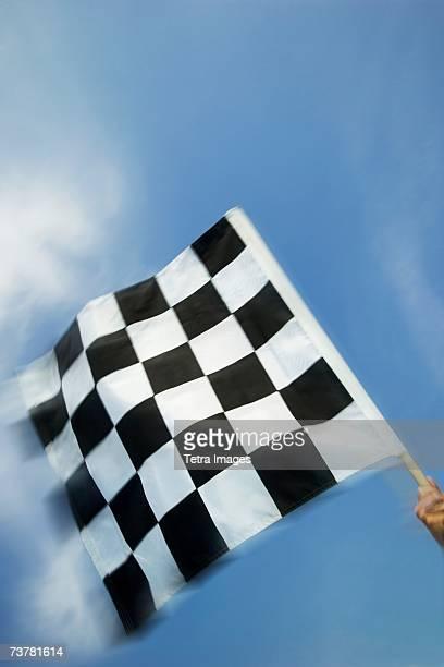 Hand waving checkered flag
