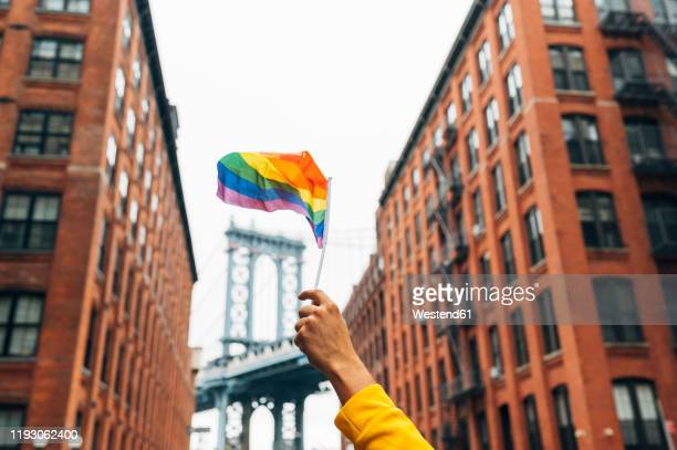 hand waving lgbt flag in nyc, usa - lgbtq stock pictures, royalty-free photos & images
