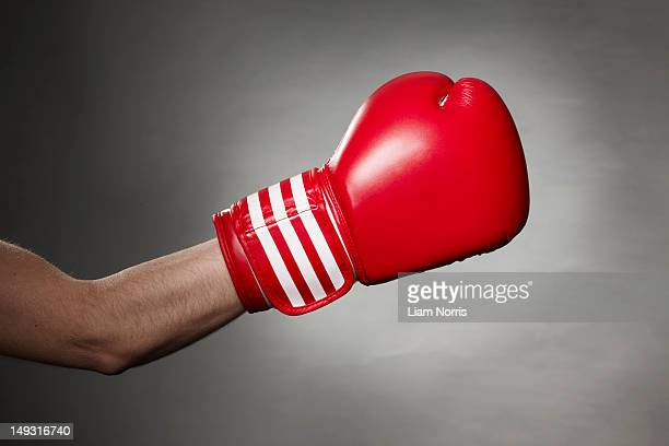 hand wearing boxing glove - boxing gloves stock photos and pictures