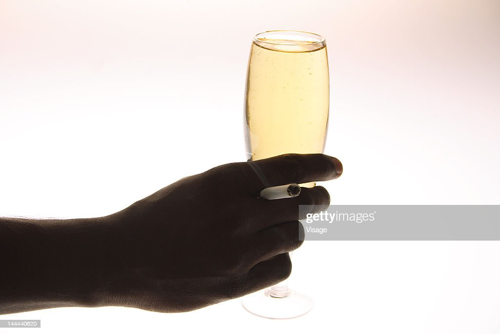 Hand with a Champagne glass and a cigarette : Stock Photo