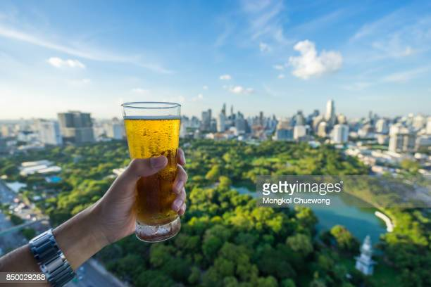 Hand with a glass of the beer against the background of Bangkok skyline Panorama ,Aerial view of Bangkok modern office buildings and condominium in Bangkok city downtown  at Bangkok , Thailand. Lumpini park