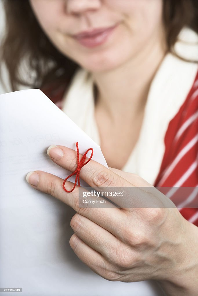A hand with a thread tied around one finger to remember Sweden. : Stock Photo