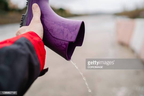 hand with a waterproof boot - purple shoe stock pictures, royalty-free photos & images