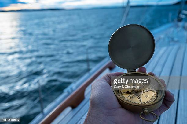 Hand with antique compass on sailboat