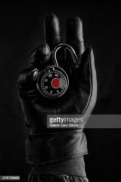 hand with black glove holding a padlock - black glove stock pictures, royalty-free photos & images