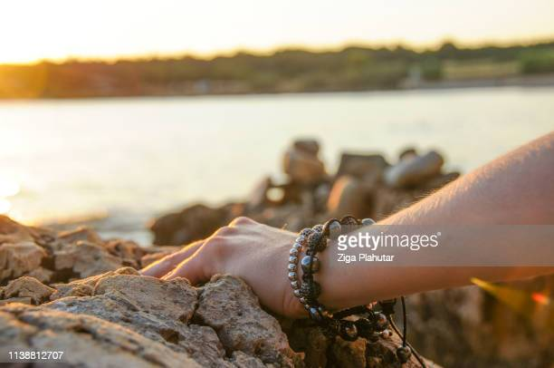 hand with bracelets by the seaside - republic of cyprus stock pictures, royalty-free photos & images