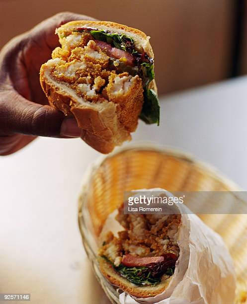 hand with fried catfish po'boy - new orleans stock pictures, royalty-free photos & images