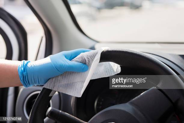 hand with glove wiping car steering wheel. - disinfection stock pictures, royalty-free photos & images
